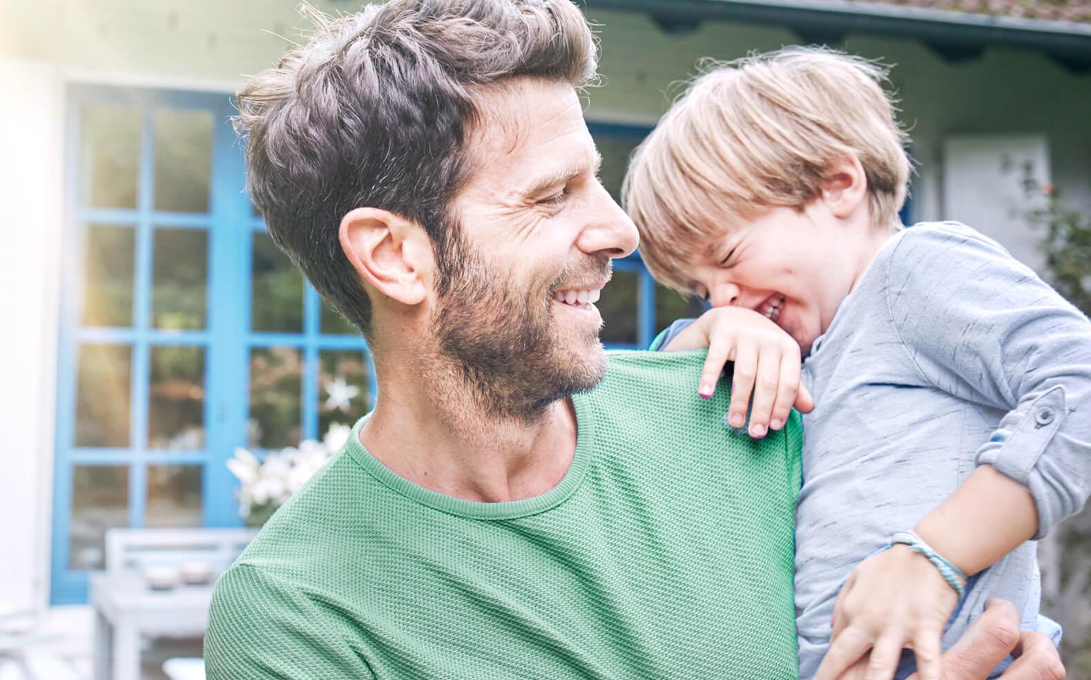 Úspěšný ETF investor smějící se a držící syna v náručí