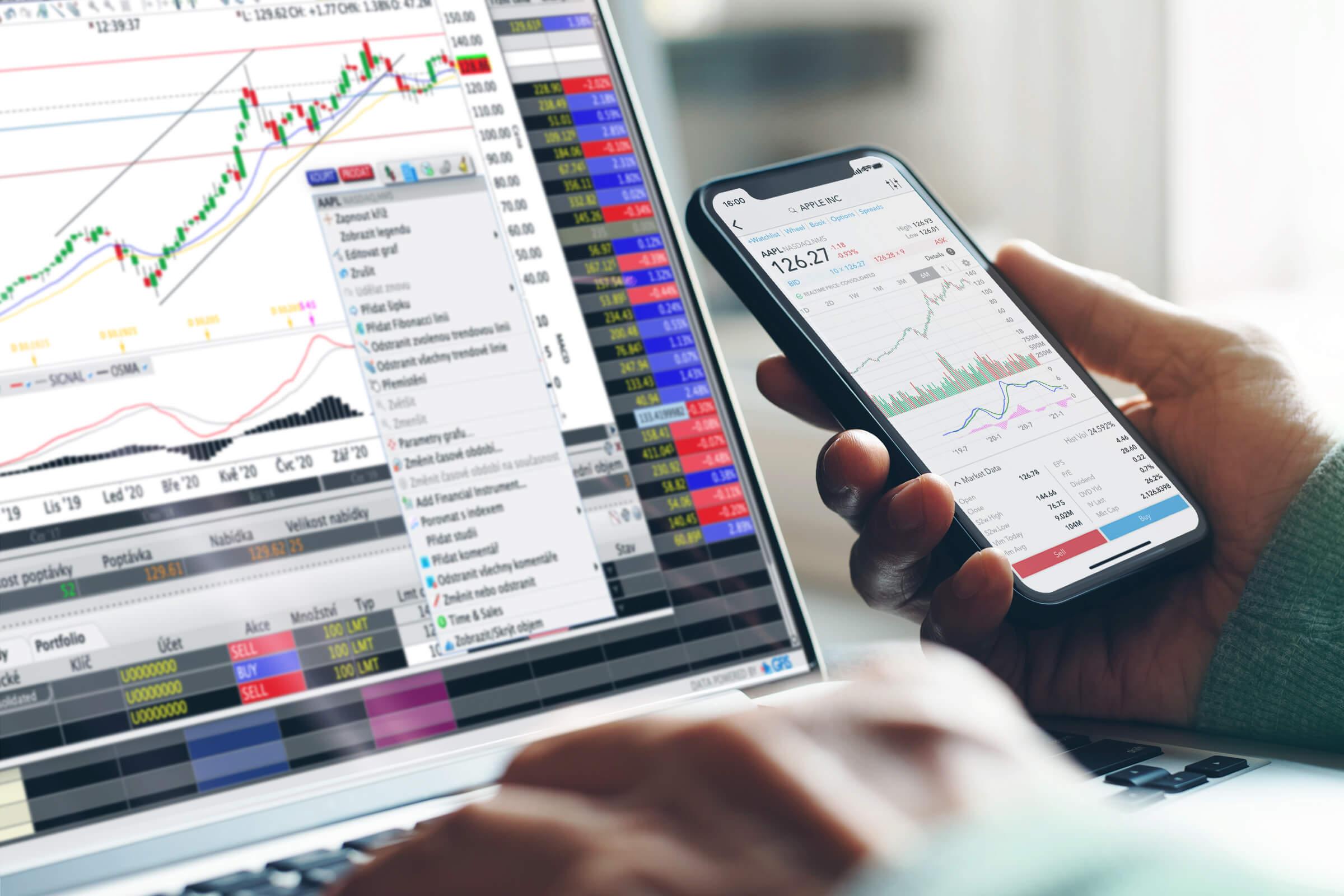 Mobilní telefon a laptop s otevřenými obchodními platformami, přes které můžete obchodovat u LYNX
