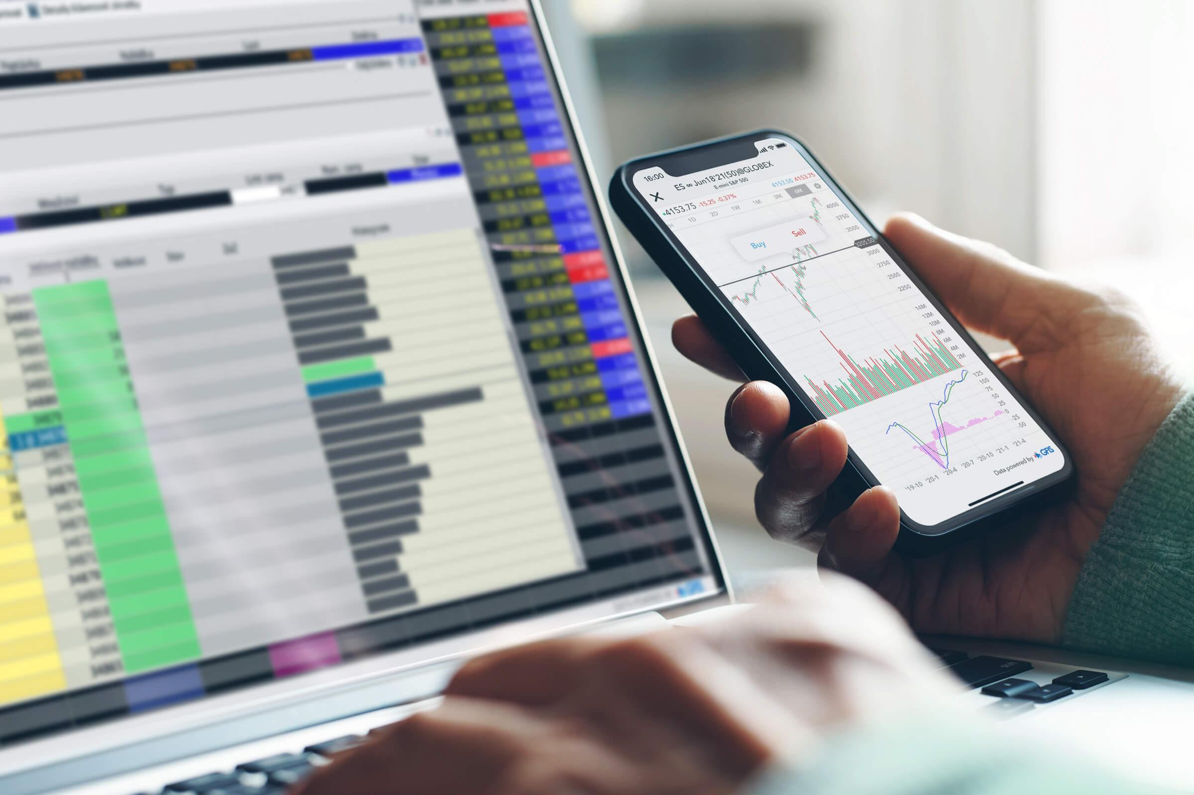 Investor a klient online brokera LYNX obchodující futures na laptopu i mobilním telefonu