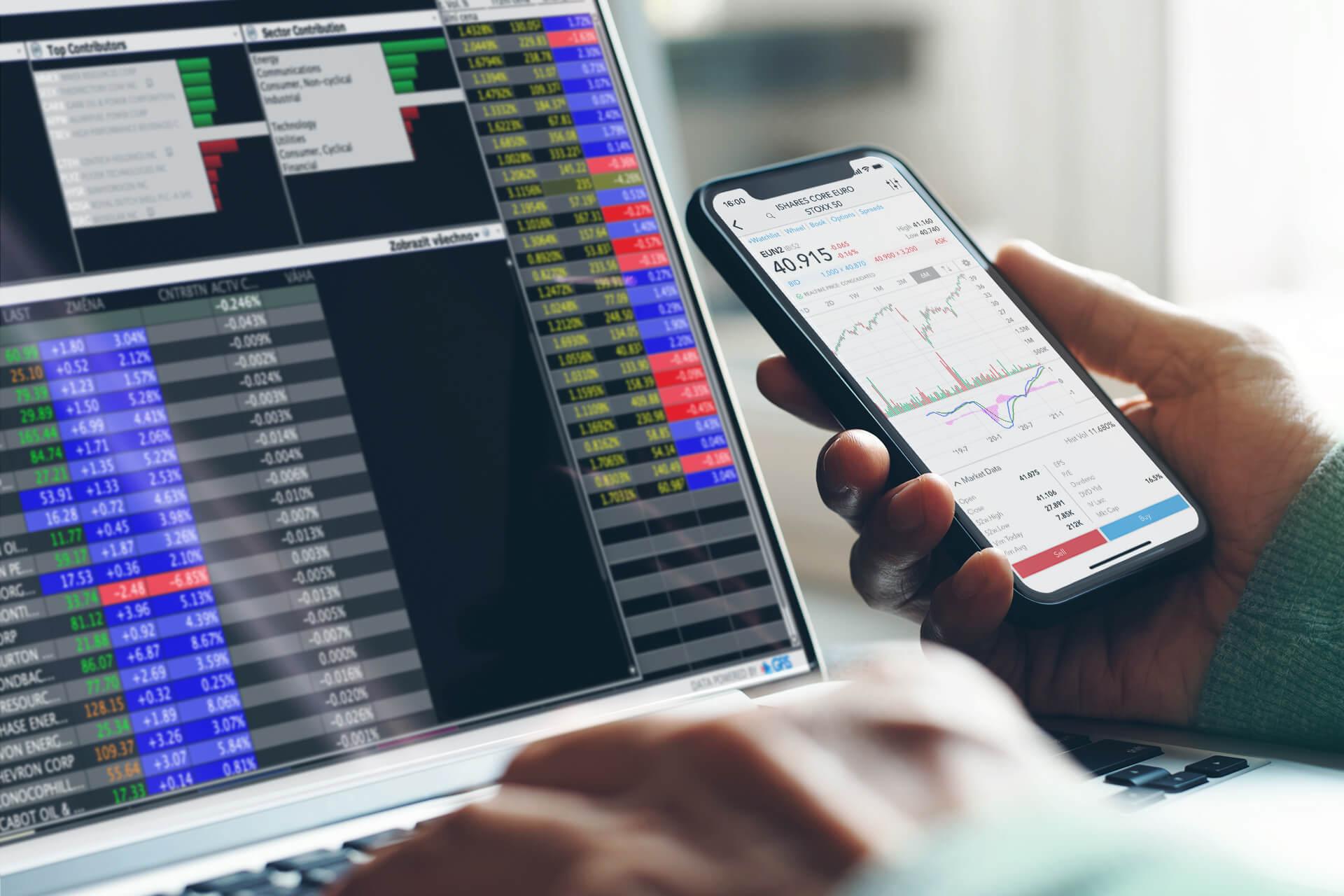 Klient LYNX obchodující ETF na laptopu a kontrolující cenový graf prostřednictvím mobilní obchodní aplikace