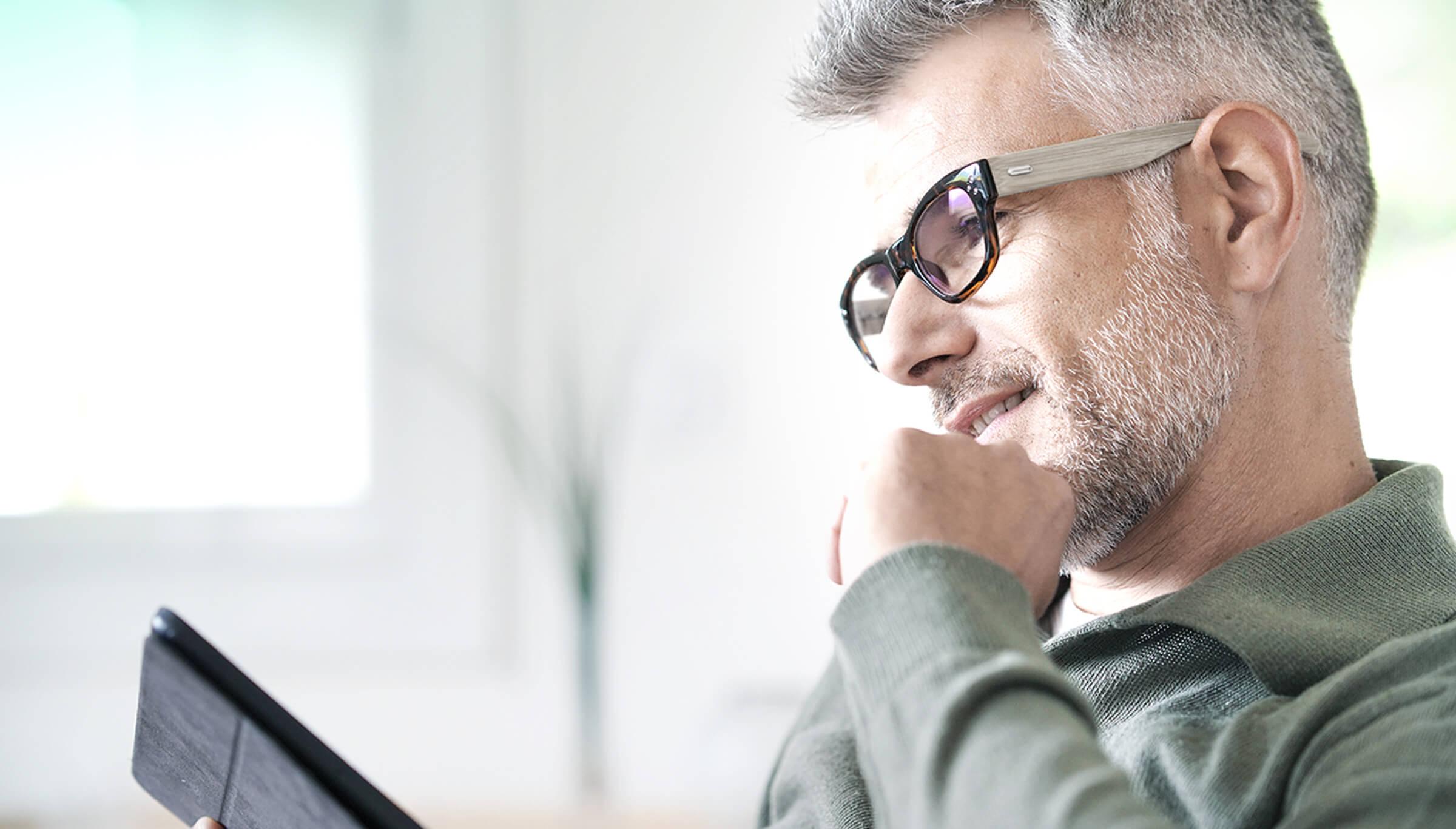 Spokojený investor a klient LYNX kontrolující své investiční portfolio na tabletu