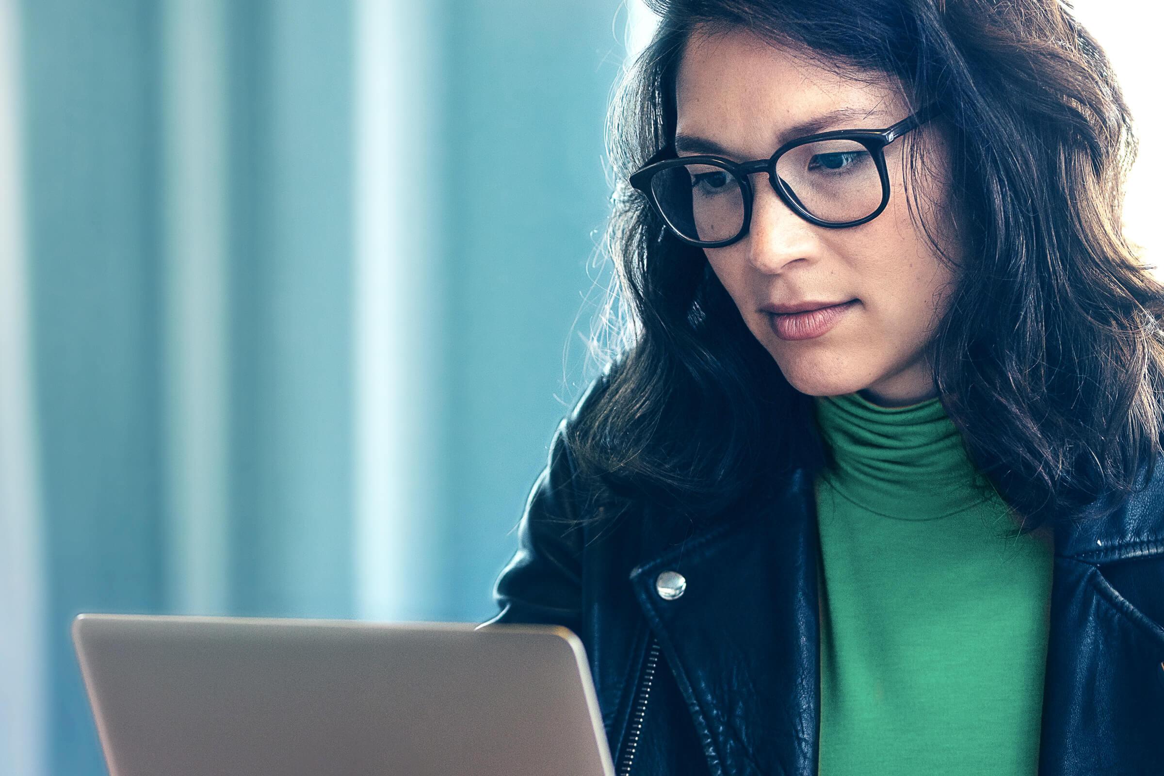Investorka s brýlemi která si právě otevírá investiční účet prostřednictvím online brokera LYNX