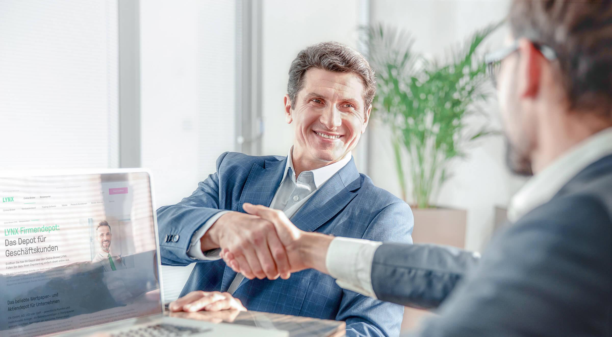 Nadšený investor podávající si ruku s pracovníkem LYNX poté, co si otevřel firemní účet