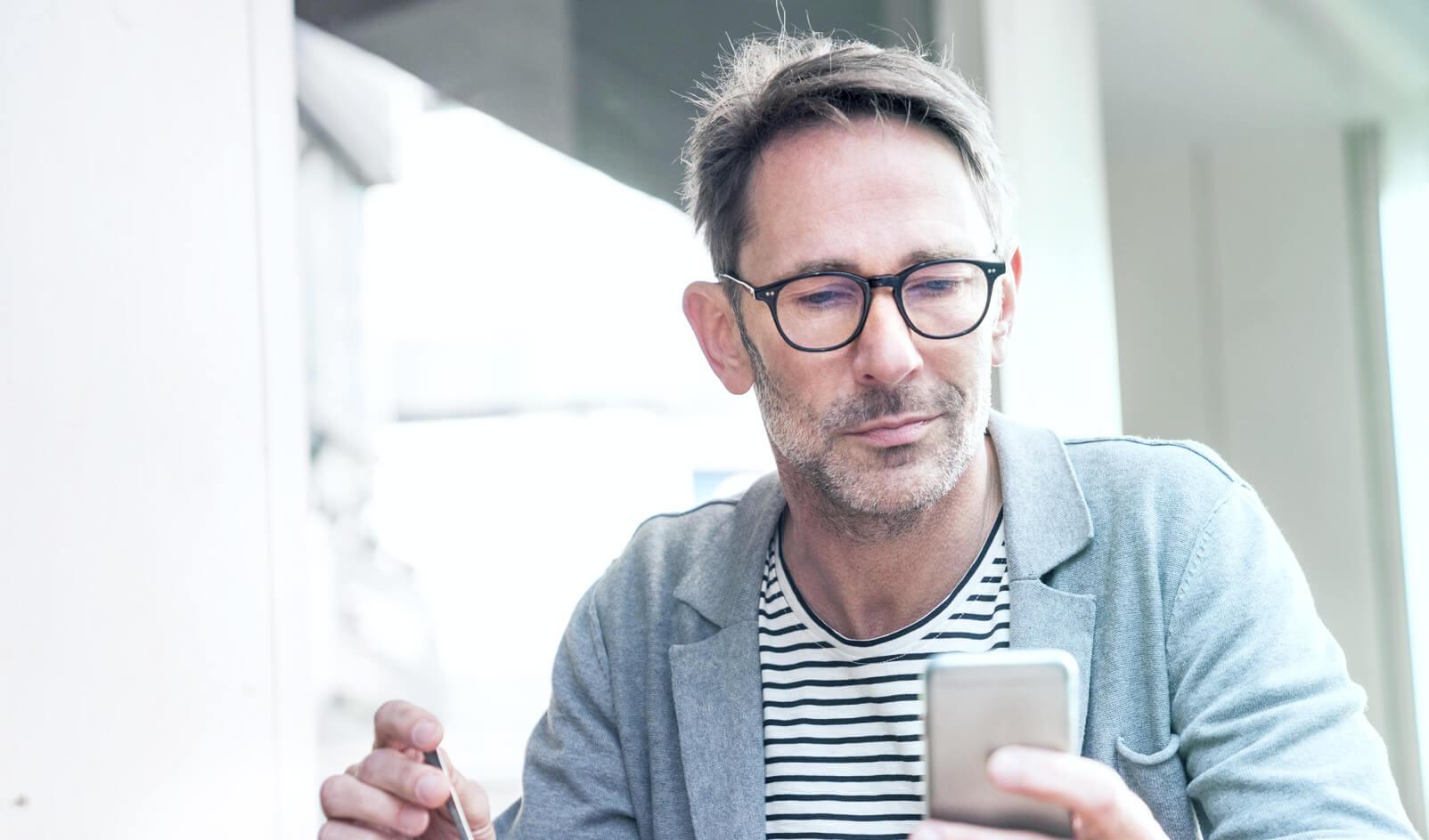 Spokojený investor a klient LYNX který obchoduje na burze za použití smartphonu