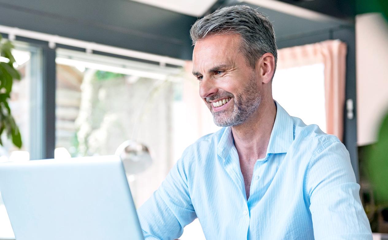 Spokojený investor v modré košili hledící do notebooku na své investiční portfolio